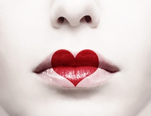 Close up of female lips with red heart shape painted on it